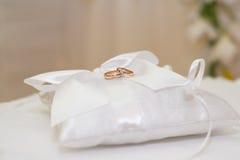 Wedding rings lying on white cushion. Elegant wedding ring looks beautiful on a white wedding pillow Royalty Free Stock Photos