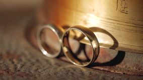 Wedding rings macro closeup gold and silver diamond jewellery in sunlights. Jewellery macro highlight wedding rings couple symbol of happiness stock footage