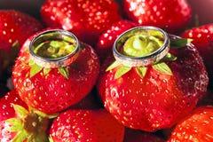 Wedding rings macro on strawberry Stock Images