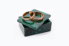 Wedding rings on a malachite box. Wedding rings of white and red gold on a green malachite box Stock Photography