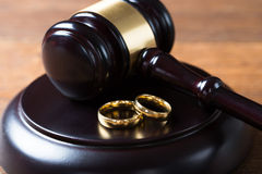Wedding Rings On Mallet In Courtroom. Closeup of wedding rings on wooden mallet at table in courtroom Royalty Free Stock Photography