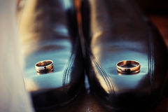 Wedding rings on a man's shoes. Wedding rings on groom's black shoes Stock Images