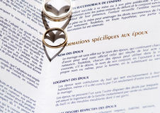 Wedding Rings and Marriage Certificate. Two wedding rings on a marriage certificate. Shallows from the rings make two hearts Stock Photo