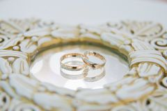 Wedding rings with reflection in mirror. Wedding rings on the mirror surface stock images