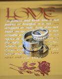 Wedding rings on mirrored glass. These are my wedding rings onto of a mirrored glass with the love scripture Royalty Free Stock Photos