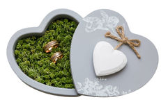 Wedding rings in moss, in the gray box in the shape of a heart. Royalty Free Stock Photo