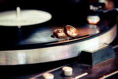 Wedding rings on a musical disc. Two wedding golden rings lie on a musical disc player royalty free stock photos