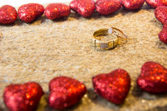 Wedding rings on a natural stone with inclusions of native gold. Offer hands and hearts. Stock Photo