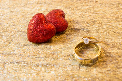 Wedding rings on a natural stone with inclusions of native gold. Offer hands and hearts. Stock Photography