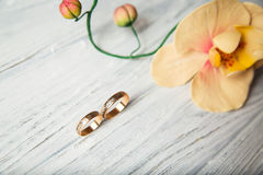 Wedding rings. Near the orchid on the wooden background Royalty Free Stock Photos