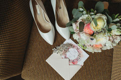 Wedding rings near shoes and invitation Stock Image