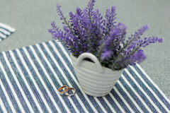 Wedding rings near vase with lavender on tablecloth Royalty Free Stock Image