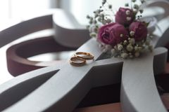 Wedding rings near the window waiting for the bride with small flowers stock images
