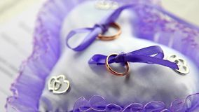 Wedding rings newlyweds lie on the soft pillow. Elegant wedding rings on a pillow with lavender lace, zoom, macro stock footage