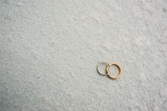 Wedding rings of newlyweds in the snow. Engagement gold rings Stock Photo