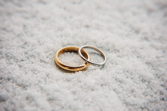 Wedding rings of newlyweds in the snow. Engagement gold rings Royalty Free Stock Photos