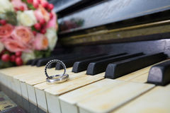 Wedding rings on old piano tiles. Royalty Free Stock Image