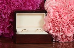 Wedding rings in an ornamental box. Golden wedding rings in a decorative box decorated with flowers royalty free stock photos