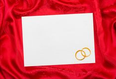 Wedding rings and paper card. On red cloth Stock Image