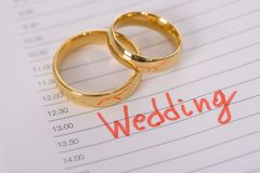 Wedding rings on paper with time Stock Images