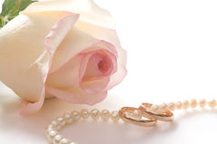 Wedding rings, pearl beads and rose, isolated Royalty Free Stock Photography