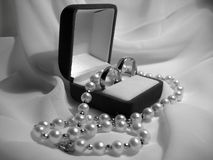 Wedding rings and pearl necklace Stock Photos
