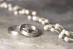 Wedding rings and pearl necklace Stock Photo