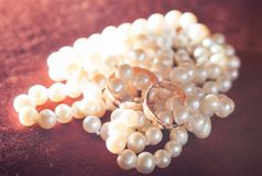 Wedding rings on pearl necklace Stock Photo