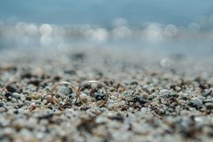 Wedding rings on the pebble sand on the beach Stock Image
