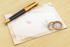 Wedding rings, pen and empty card on wooden table Stock Images