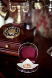 Wedding rings on the phone. Engagement ring in a box at the phone on brown Royalty Free Stock Photos