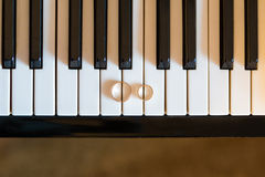 Wedding rings on piano. Golden wedding rings on piano Royalty Free Stock Photo