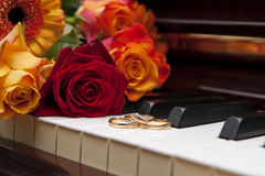 Wedding Rings on a piano keyboard and Flowers. A Romantic image displaying golden marriage rings on the keyboard of an old wooden piano and there are reddish Stock Image