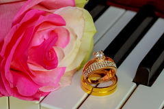 Wedding Rings on a piano keyboard and Flowers Royalty Free Stock Photos