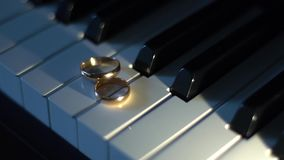 Wedding rings on piano keys-3. Wedding rings on piano keys. Point source of light stock video footage