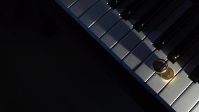 Wedding rings on piano keys-2. Wedding rings on piano keys. Point source of light stock video