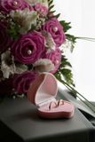 Wedding rings in a pink box. Of the form of heart near to a bouquet of the bride Royalty Free Stock Image