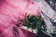 Wedding rings on a pink cloth in a wreath of green, silver in the background royalty free stock photography
