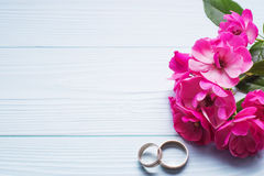Wedding rings with pink roses on a blue wooden background. Stock Image