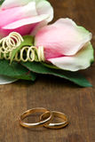 Wedding rings with pink roses Stock Photo