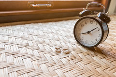 Wedding rings place on table and alarm clock Stock Image
