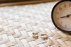Wedding rings place on table and alarm clock Royalty Free Stock Images