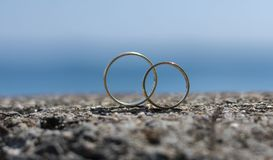 Wedding rings placed on a rock stock image