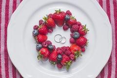 Wedding rings on plate with berries. Wedding rings on plate with fresh berries Stock Photo