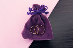 Wedding rings on a purple bag. Wedding rings in the purple bag on a table with a purple cloth Royalty Free Stock Photo