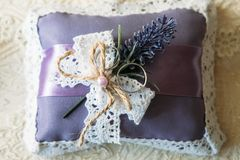 Wedding rings on a purple cushion. Decorated with lace and a sprig of lavender royalty free stock images