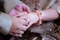 Wedding rings. He Put the Wedding Ring on Her. Close up Groom Put the Ring on bride. thai wedding ceremony stock photos