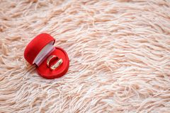 Wedding rings in a red box on a beige plaid with copy space. Gold wedding rings in a red box on a furry beige plaid with a copy of space stock image
