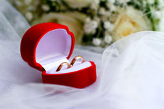 Wedding rings in a red box and a bouquet close-up Royalty Free Stock Photos