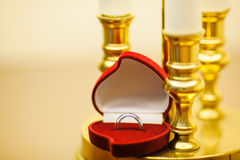 Wedding Rings in Red Box near Candle Holders. Wedding rings in red heart shape box near candle holders. Female and male platinum rings. Jewelry in container royalty free stock photo